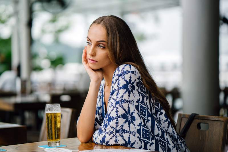 A woman sitting with a drink.