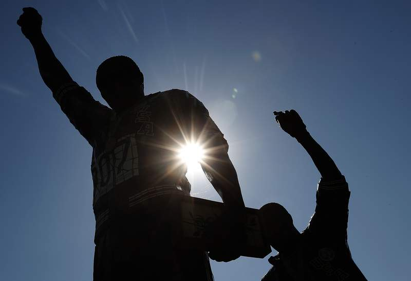 FILE - In this Oct. 17, 2018, file photo, a statue in honor of former Olympians Tommie Smith, left, and John Carlos is seen on the campus of San Jose State University in San Jose, Calif.  Smith and Carlos raised their black-gloved fists while their national anthem played during the 200-meters medals ceremony at the Mexico City Olympics in 1968. Rule 50 of the IOC charter states: No kind of demonstration or political, religious or racial propaganda is permitted in any Olympic sites, venues or other areas. (AP Photo/Tony Avelar, File)
