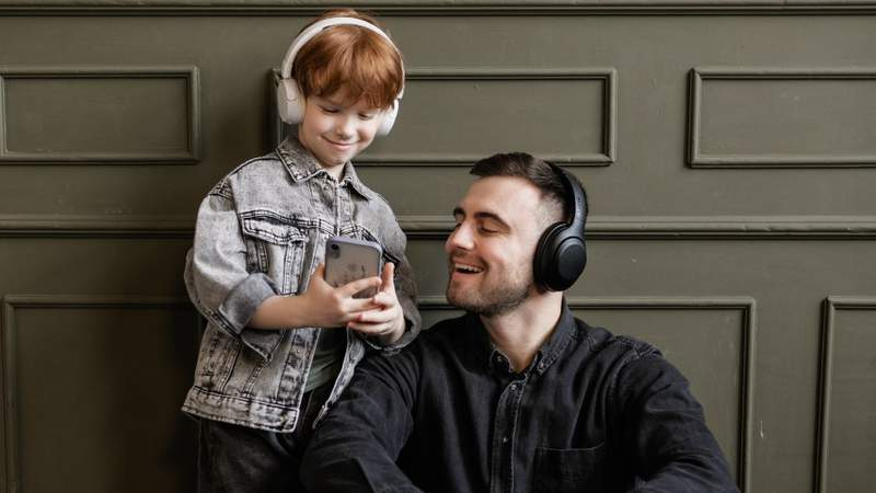 A father and son listen to music together.