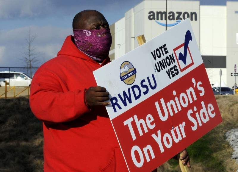 FILE - In this Tuesday, Feb. 9, 2021, file photo, Michael Foster of the Retail, Wholesale and Department Store Union holds a sign outside an Amazon facility where labor is trying to organize workers in Bessemer, Ala. Nearly 6,000 Amazon warehouse workers in Bessemer are deciding whether they want to form a union, the biggest labor push in the online shopping giant's history. Mail-in voting started in early February. Ballots must be received by the end of Monday March 29, 2021. The National Labor Relations Board starts counting votes the next day. (AP Photo/Jay Reeves, File)