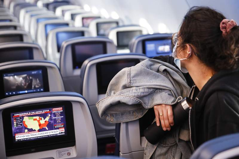 A passenger wears personal protective equipment on a Delta Airlines flight as a map depicting the spread of COVID-19 is displayed on a monitor after landing at MinneapolisSaint Paul International Airport, Thursday, May 28, 2020, in Minneapolis. (AP Photo/John Minchillo)