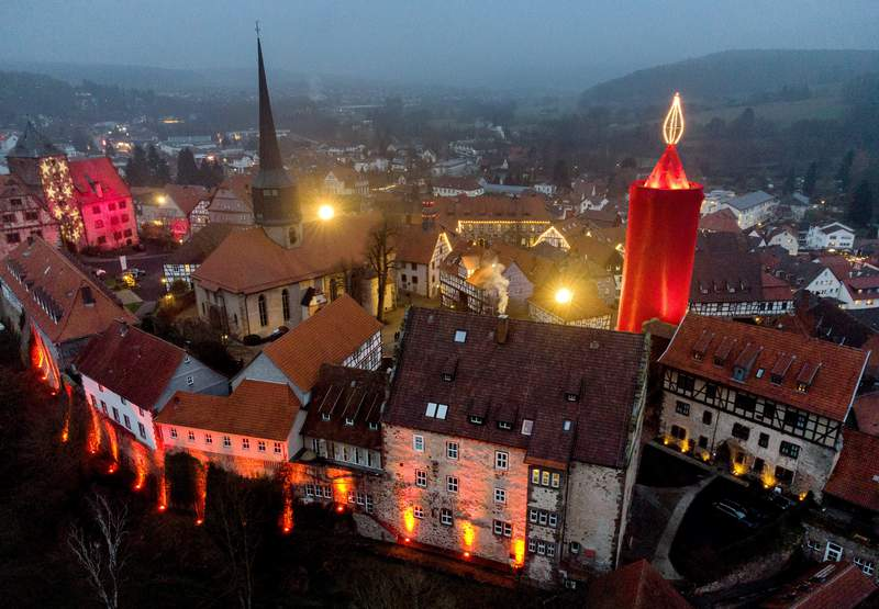 "One of the world's largest Christmas candles shines in the city of Schlitz, central Germany, Sunday, Dec.6, 2020. The candle consists of a historic stone tower wrapped in red cloth, with 110 light bulbs mounted at its tip to form a six-metre high ""flame"". This brings the candle to a total height of 42 metres. (AP Photo/Michael Probst)"
