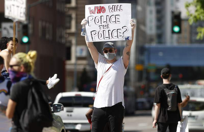 A demonstrator wears a face mask and latex gloves while waving a placard along Lincoln Avenue during a protest Tuesday, June 2, 2020, in Denver over the death of George Floyd, a handcuffed black man in police custody in Minneapolis. (AP Photo/David Zalubowski)