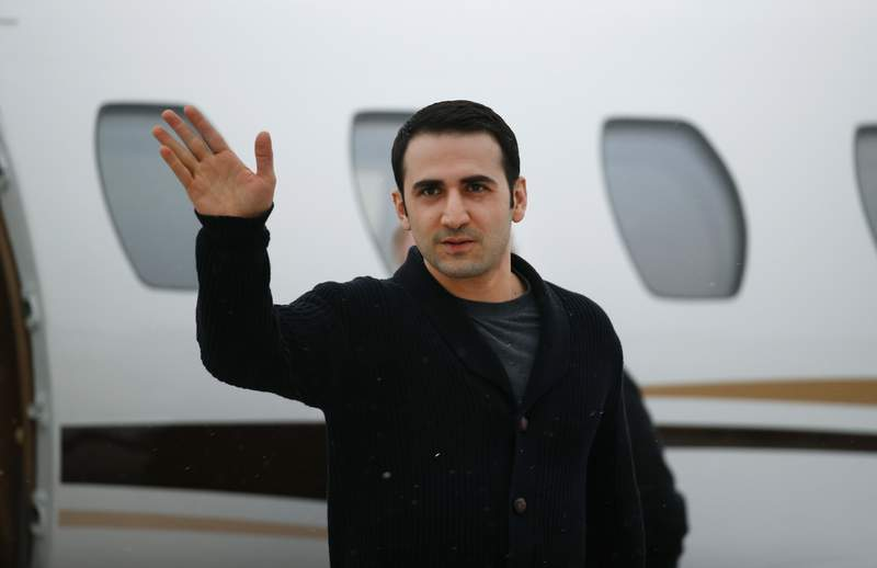 FILE - In this Jan. 21, 2016, file photo, Amir Hekmati waves after arriving on a private flight at Bishop International Airport in Flint, Mich. A judge has thrown out a lawsuit from the former Marine who was jailed in Iran for more than four years and then denied a multimillion-dollar payout from a special U.S. government victims fund after an FBI espionage investigation into his travels.(AP Photo/Paul Sancya, File)