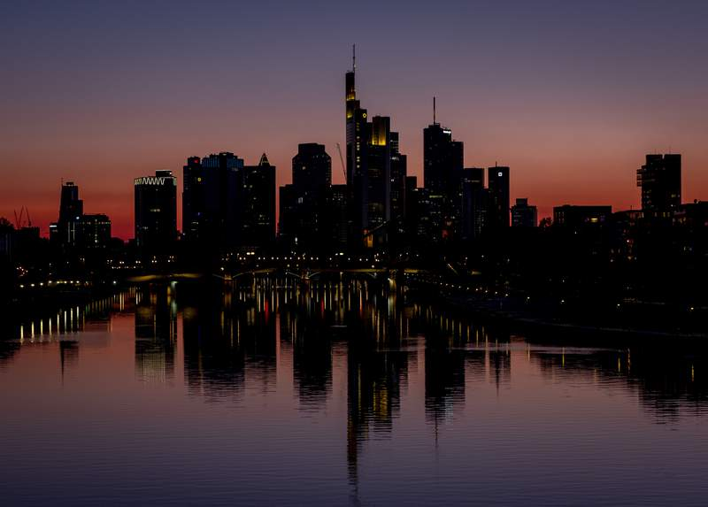 The buildings of the banking district are reflected in the river Main in Frankfurt, Germany, Saturday, April 25, 2020. Due to the coronavirus the economy worldwide expects heavy losses. (AP Photo/Michael Probst)