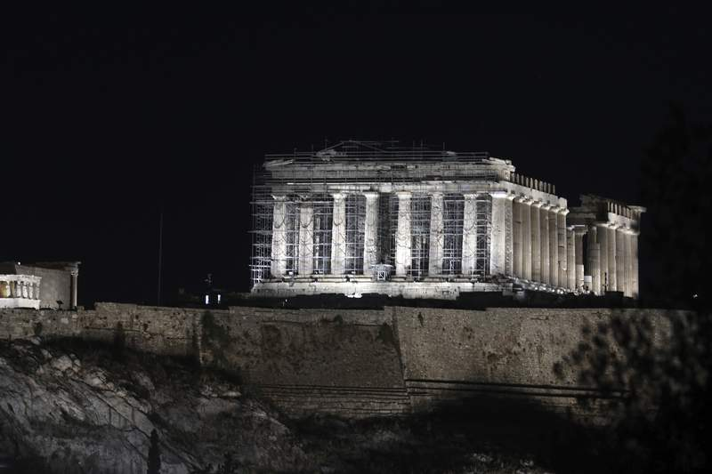 A new lighting system illuminates the ancient Acropolis hill in Athens, Wednesday, Sept. 30, 2020. Ancient temples on the Acropolis are illuminated after a new lighting system was installed and launched. The lower-energy LED lighting fixtures will light up more parts of the ancient site and is also intended to reduce light pollution with better-targeted lighting. (AP Photo/Yorgos Karahalis)