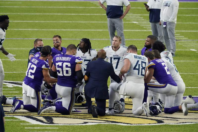 Tennessee Titans and the Minnesota Vikings players meet at midfield following an NFL football game, Sunday, Sept. 27, 2020, in Minneapolis. Tennessee won 31-30. The NFL says the Tennessee Titans and Minnesota Vikings are suspending in-person activities after the Titans had three players test positive for the coronavirus, along with five other personnel. The league says both clubs are working closely with the NFL and the players union on tracing contacts, more testing and monitoring developments. The Titans are scheduled to host the Pittsburgh Steelers on Sunday.(AP Photo/Jim Mone)