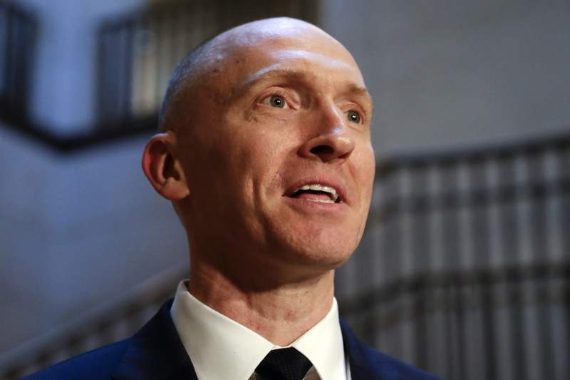 FILE - In this Nov. 2, 2017, photo, Carter Page, a foreign policy adviser to Donald Trump's 2016 presidential campaign, speaks with reporters following a day of questions from the House Intelligence Committee, on Capitol Hill in Washington.  Page, who was the target of a secret surveillance warrant during the FBIs Russia investigation says in a federal lawsuit filed Friday, Nov. 27, 2020,  that he was the victim of unlawful spying. The suit from Carter Page alleges a series of omissions and errors made by FBI and Justice Department officials in applications they submitted to the Foreign Intelligence Surveillance Court to eavesdrop on Page on suspicion that he was an agent of Russia.(AP Photo/J. Scott Applewhite)