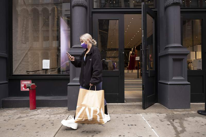 A customer walks out of a Zara store, Thursday, March 25, 2021, in New York.  U.S. consumer confidence rose sharply for a second straight month in April, hitting the highest level in more than a year as consumer sentiment was boosted by a more rapid rollout of the vaccines and another round of support payments. (AP Photo/Mark Lennihan)