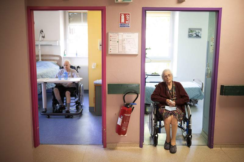 FILE - In this April 16, 2020 file photo, Marie Lithard, right, and her neighboor Yves Chretien sit looking out of their rooms in a nursing home in Ammerschwir, France. The French government announced Saturday Dec. 12, 2020, it is giving care home residents more freedom for the end of year holidays, allowing them out to spend time with their families and receive visits even if they are positive for COVID-19. (AP Photo/Jean-Francois Badias, File)