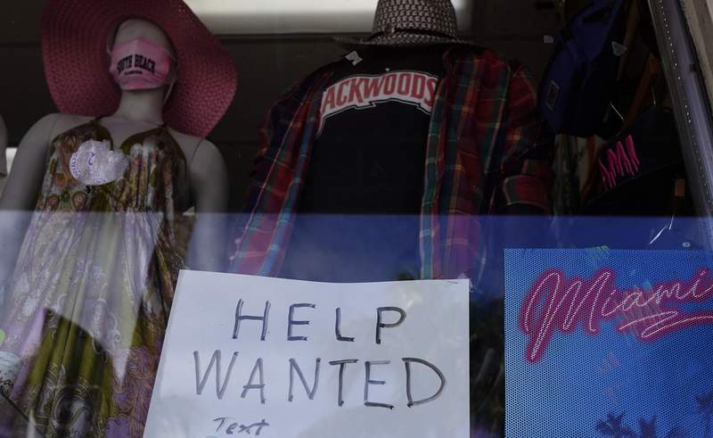 """A """"Help Wanted,"""" sign is shown in the window of a souvenir shop, Thursday, Jan. 7, 2021, in Miami Beach, Fla.  Layoffs spiked in November compared with the previous month and the number of job openings slipped, a sign the job market has stalled as the resurgent coronavirus has forced new shutdowns of restaurants and bars and discouraged consumer spending.  (AP Photo/Wilfredo Lee)"""