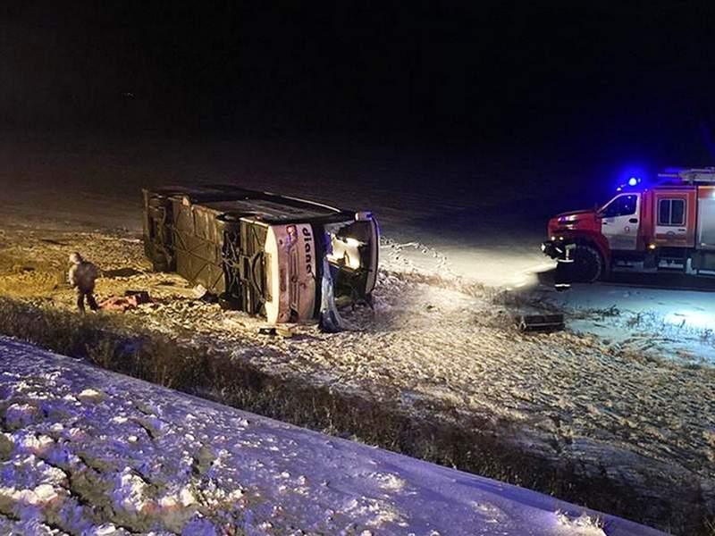 This photo provided by the Government of Ryazan Region of Russia Press Office shows a bus which fell off a road near Vysokoye village, Russia, early Friday, Dec. 25, 2020. At least four people have died and another 11 have been injured when an intercity bus fell off a road in western Russia. The bus driving from Moscow to Volgograd veered into a ditch and overturned in the Ryazan region, about 250 kilometers (about 155 miles) south of Moscow early Friday. (Government of Ryazan Region of Russia Press Office via AP)