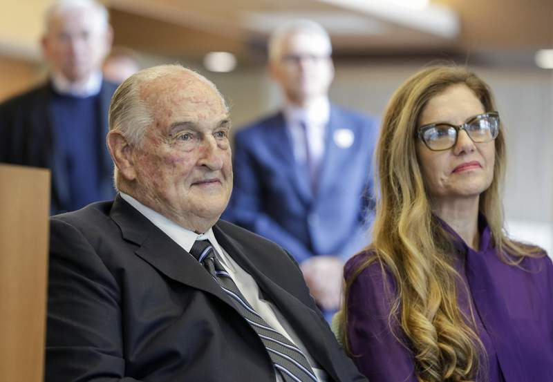 FILE - Philanthropist Walter Scott, left, sits next to Leslie Jackson, wife of glass artist Dale Chihuly during a ceremony at the Fred & Pamela Buffett Cancer Center in Omaha, Neb., Friday, May 19, 2017. Billionaire Scott, the past top executive of Peter Kiewit Sons Inc. construction firm who helped oversee Warren Buffetts conglomerate and donated to various causes, particularly construction projects around Omaha, died, Saturday, Sept. 25, 2021. He was 90. (AP Photo/Nati Harnik, File)