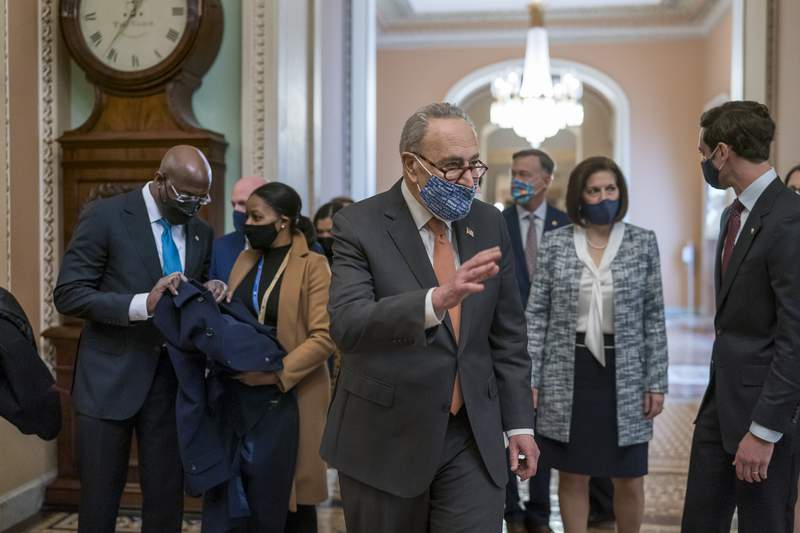 On the first full day of Democratic control, Senate Majority Leader Chuck Schumer, D-N.Y., walks to the chamber after meeting with new senators from his caucus, at the Capitol in Washington, Thursday, Jan. 21, 2021. From left are Sen. Raphael Warnock, D-Ga., Schumer, Sen. John Hickenlooper, D-Colo., rear, Sen. Catherine Cortez Masto, D-Nev., who chairs the Democratic Senatorial Campaign Committee, and Sen. Jon Ossoff, D-Ga. The pivotal Georgia runoff election this month was decisive in handing Democrats the majority in the Senate. (AP Photo/J. Scott Applewhite)