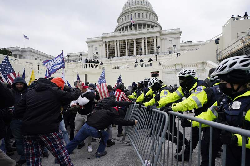 FILE - In this Jan. 6, 2021 file photo, Trump supporters try to break through a police barrier at the Capitol in Washington. With riot cases flooding into Washingtons federal court, the Justice Department is under pressure to quickly resolve the least serious cases. (AP Photo/Julio Cortez, File)