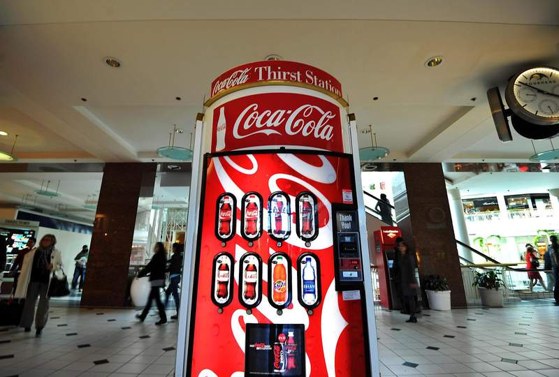 People walk past a Coca-Cola vending machine at a shopping mall in Arlington, Va. Jewel Samad / AFP (NBC News)