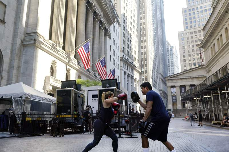 A woman and her trainer workout outside the New York Stock Exchange, Monday, June 7, 2021. Stocks are nudging mostly higher in early trading, putting the S&P 500 and the Dow Jones Industrial Average back near the record highs they reached a month ago. (AP Photo/Richard Drew)