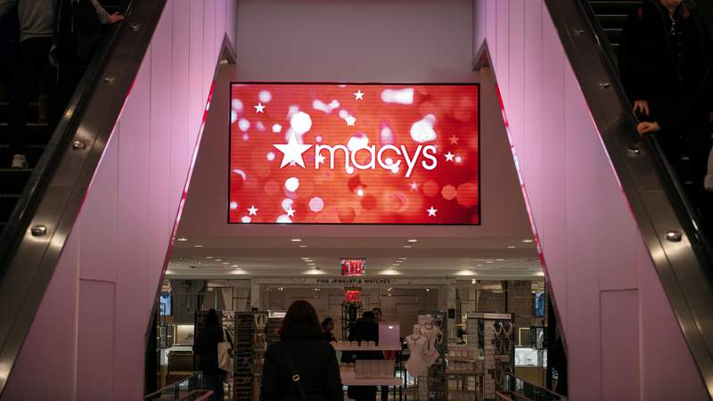 Shoppers pass by an illuminated sign inside the Macy's flagship store on 34th Street in Midtown Manhattan on February 25, 2020 in New York City. Earlier in February, Macy's announced it was closing 125 department stores and laying off 2,000 corporate employees amidst falling profits and revenue.