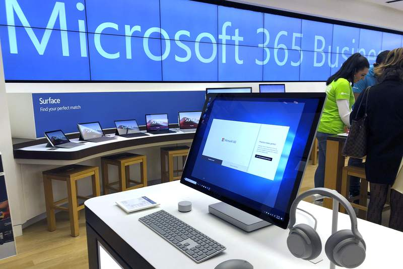 FILE - In this Jan. 28, 2020, file photo a Microsoft computer is among items displayed at a Microsoft store in suburban Boston. Microsoft says its supply chain is being hurt by the virus outbreak in China and will return to normal operations at a slower pace than it expected a month ago. (AP Photo/Steven Senne, File)