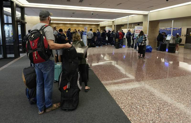 Passengers queue up at the ticketing counter for Southwest Airlines flights in Eppley Airfield Sunday, Oct. 10, 2021, in Omaha, Neb. Southwest Airlines canceled hundreds of flights over the weekend, blaming the woes on air traffic control issues and weather. (AP Photo/David Zalubowski)