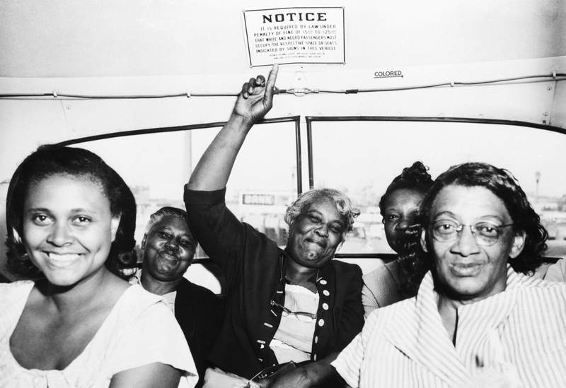 A passenger points to one of the segregation signs removed from all Dallas Transit Company buses, following a Supreme Court ruling banning segregation on all public transportation within a state, on April 25, 1956.
