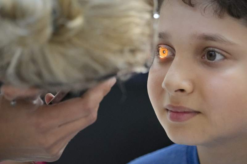FILE - In this  Saturday, May 29, 2021 file photo, A boy undergoes an eyesight examination performed by volunteer ophthalmologists, in Nucsoara, Romania. The U.N. General Assembly approved its first-ever resolution on vision Friday, July 23, 2021 calling on its 193 member nations to ensure access to eye care for everyone in their countries which would contribute to a global effort to help at least 1.1 billion people with vision impairment who currently lack eye services by 2030. The Vision for Everyone resolution, sponsored by Bangladesh, Antigua and Ireland, and co-sponsored by over 100 countries, was adopted by consensus by the world body. (AP Photo/Vadim Ghirda, File)