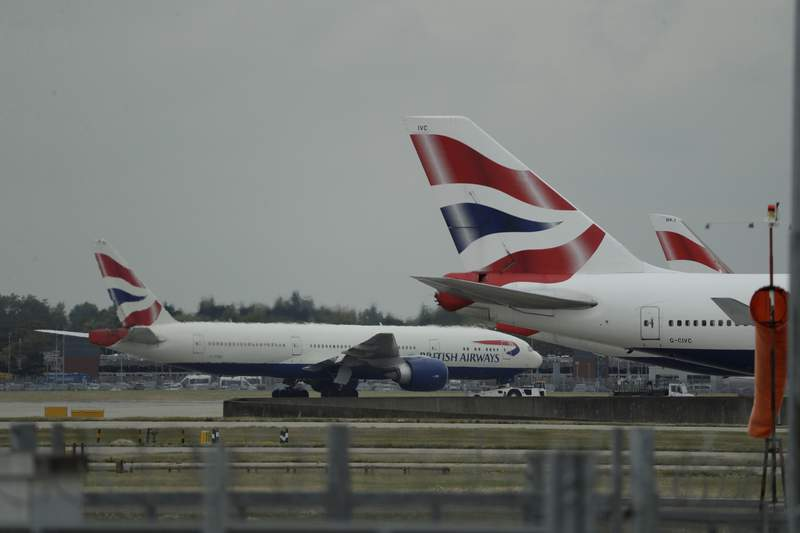 FILE - In this Monday, Sept. 9, 2019 file photo, a British Airways plane, at left, is towed past other planes sitting parked at Heathrow Airport in London. British Airways said Tuesday Nov. 17, 2020, that it will start testing passengers flying from the U.S. to Londons Heathrow Airport for COVID-19 in an effort to persuade the British government it should scrap rules requiring most international travelers to quarantine for 14 days. (AP Photo/Matt Dunham, File)