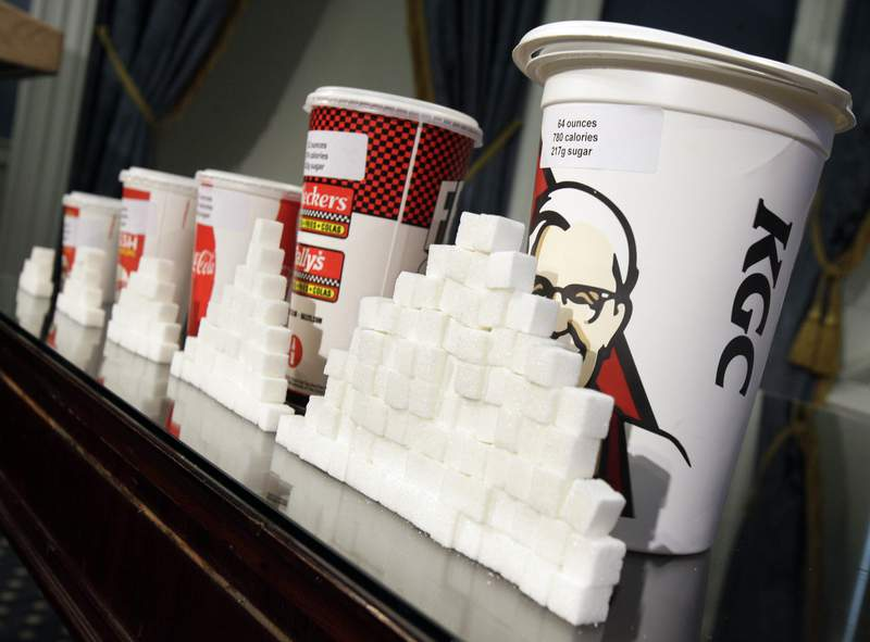 FILE - This May 31, 2012 file photo shows a display of various size cups and sugar cubes at a news conference at New York's City Hall. A range of factors contribute to childhood obesity, including eating a lot of processed foods and sugary beverages, and a lack of physical exercise. (AP Photo/Richard Drew, File)