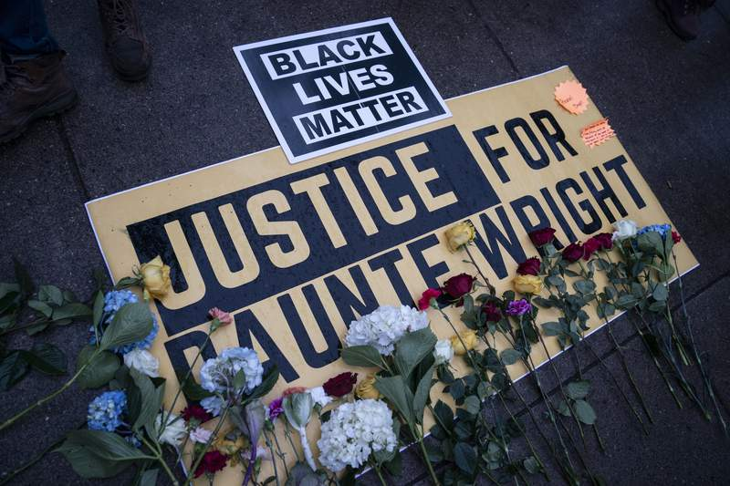 Flowers have been placed on a banner as demonstrators gather outside the Brooklyn Center (Minn.) Police Department on Tuesday, April 13, 2021, to protest Sunday's fatal shooting of Daunte Wright during a traffic stop. (AP Photo/John Minchillo)