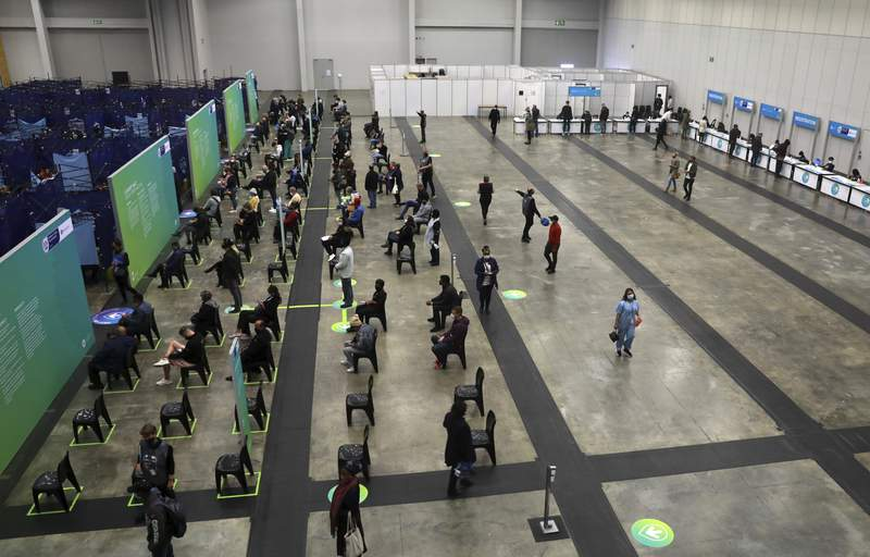 People wait to get vaccinated at the Vaccination Centre of Hope at the Cape Town International Convention Centre in Cape Town, South Africa, Tuesday Aug. 24, 2021. South Africa's Health Minister Joe Phaahla says on Friday, Sept. 3, 2021 the government will let businesses decide whether or not to make vaccinations mandatory for employees and clients. He said restaurants, bars, grocery stores and other businesses must set their own policies on whether or not to insist that patrons must be vaccinated. (AP Photo/Nardus Engelbrecht)
