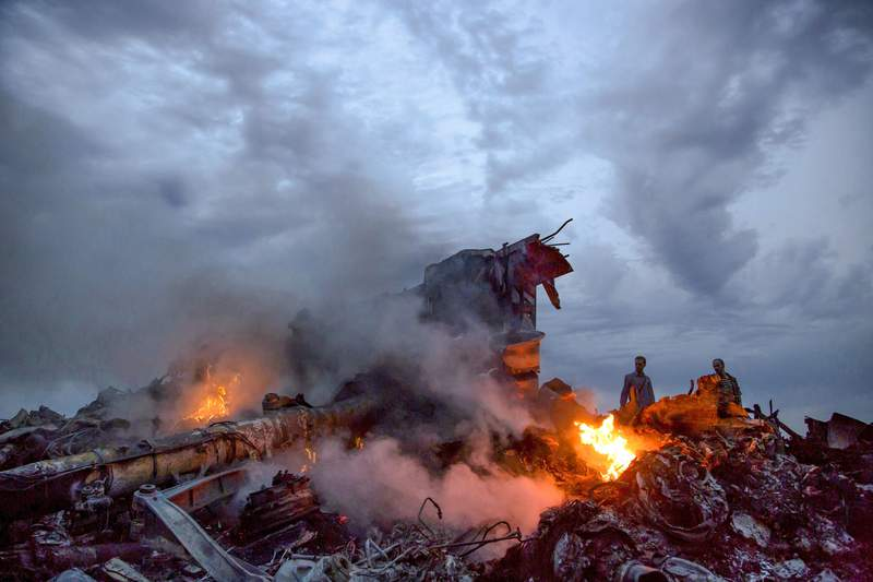 FILE - In this Thursday, July 17, 2014 file photo, people walk amongst the debris at the crash site of a Malaysia Airlines Flight 17 passenger plane near the village of Grabove, Ukraine.  Judges in The Hague, Netherlands, in the trial of three Russians and a Ukrainian who are charged with murder for their alleged roles in the deadly shooting down of Malaysia Airlines Flight 17 in 2014, will be allowed to consider testimony from 12 anonymous witnesses, according to a judicial ruling made Thursday April 23, 2020. (AP Photo/Dmitry Lovetsky, File)