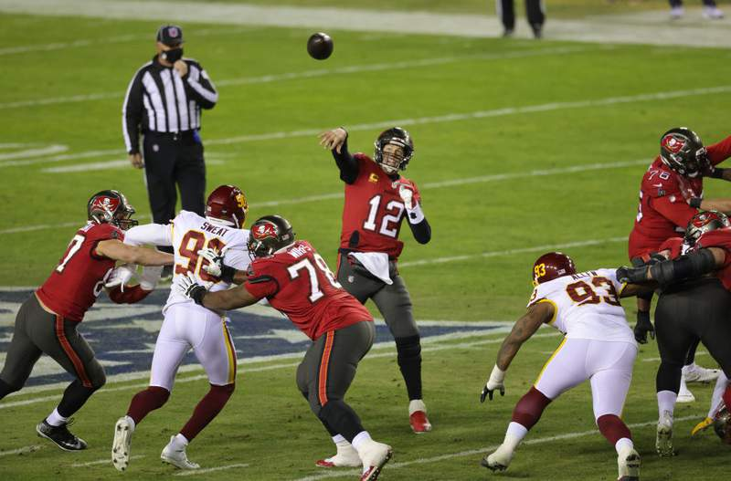LANDOVER, MARYLAND - JANUARY 09:  Quarterback Tom Brady #12 of the Tampa Bay Buccaneers throws a touchdown pass to wide receiver Antonio Brown #81 during the 1st quarter of the game against the Washington Football Team at FedExField on January 09, 2021 in Landover, Maryland. (Photo by Rob Carr/Getty Images)
