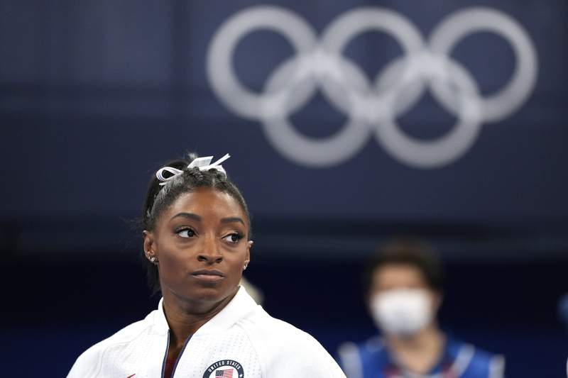 FILE - In this July 27, 2021 file photo, Simone Biles, of the United States, watches gymnasts perform after she exited the team final at the 2020 Summer Olympics, in Tokyo. Biles and Naomi Osaka are prominent young Black women under the pressure of a global Olympic spotlight that few human beings ever face. But being a young Black woman -- which, in American life, comes with its own built-in pressure to perform -- entails much more than meets the eye. (AP Photo/Ashley Landis, File)