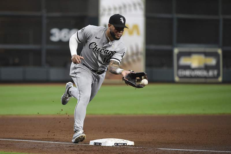 Chicago White Sox third baseman Yoan Moncada (10) fields a round ball by Houston Astros second baseman Jose Altuve (27) during the third inning in Game 2 of a baseball American League Division Series Friday, Oct. 8, 2021, in Houston. Altuve was out at first. (AP Photo/Eric Christian Smith)