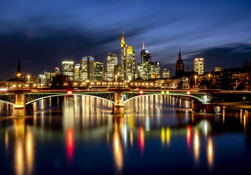 Lights of the city are reflected in the river Main in Frankfurt, Germany, Thursday, Feb. 4, 2021. In background the buildings of the banking district. (AP Photo/Michael Probst)