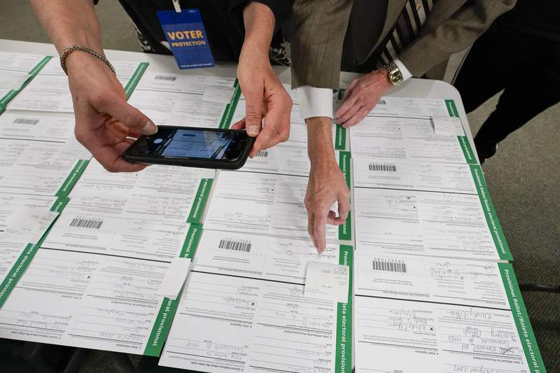 A canvas observer photographs Lehigh County provisional ballots as vote counting in the general election continues, Friday, Nov. 6, 2020, in Allentown, Pa. (AP Photo/Mary Altaffer)