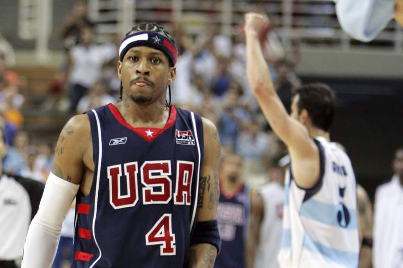 FILE - In this Aug. 27, 2004, file photo, USA's Allen Iverson (4) walks off the court as Argentina's Emanuel Ginobili celebrates at the end of their semifinal basketball game at the Olympic Indoor Hall during the 2004 Olympic Games in Athens, Greece. (AP Photo/Michael Conroy, File)