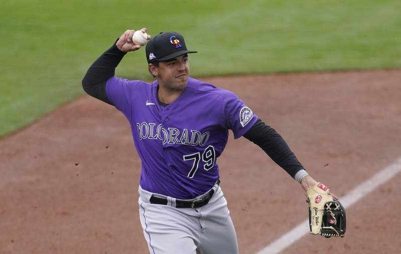 FILE - In this March 12, 2021, file photo, Colorado Rockies third baseman Colton Welker throws to first during the team's spring training baseball game against the San Francisco Giants in Scottsdale, Ariz. Colorado Rockies minor-league third baseman Welker was given an 80-game suspension after testing positive for a performance-enhancing substance. The suspension was announced Thursday, May 6, 2021, by the Office of the Commissioner of Baseball. Welker is currently on the roster for Triple-A Albuquerque. His suspension of goes into immediate effect and will be without pay. (AP Photo/Ashley Landis, File)