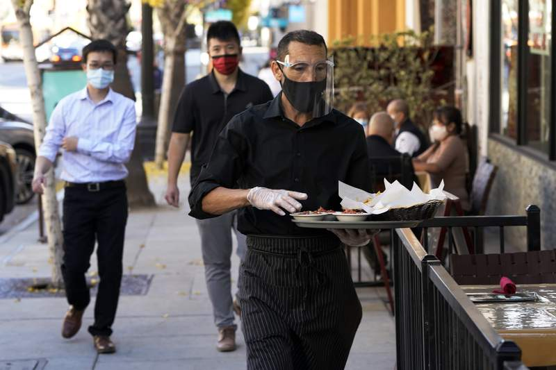 FILE - A waiter wears a mask and face covering at a restaurant with outdoor seating Tuesday, Dec. 1, 2020, in Pasadena, Calif.  The U.S. services sector, where most Americans work, registered its sixth consecutive month of expansion in November. The Institute for Supply Management reported Thursday that its index of services activity declined slightly to a reading of 55.9 last month, from a reading of 56.6 in October.  (AP Photo/Marcio Jose Sanchez, File)