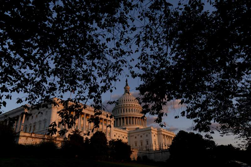 FILE - The U.S Capitol at sunset in Washington, on Sept. 30, 2021. Year-end pileups of crucial legislation and the brinkmanship that goes with it are annual rituals for Congress. But this time, testy lawmakers are barreling toward an autumn of battles that are striking for the risks they pose to both parties and their leaders. Miscalculate and there could be a calamitous federal default, a collapse of Biden's domestic agenda and, for good measure, a damaging government shutdown. (AP Photo/Andrew Harnik, File)
