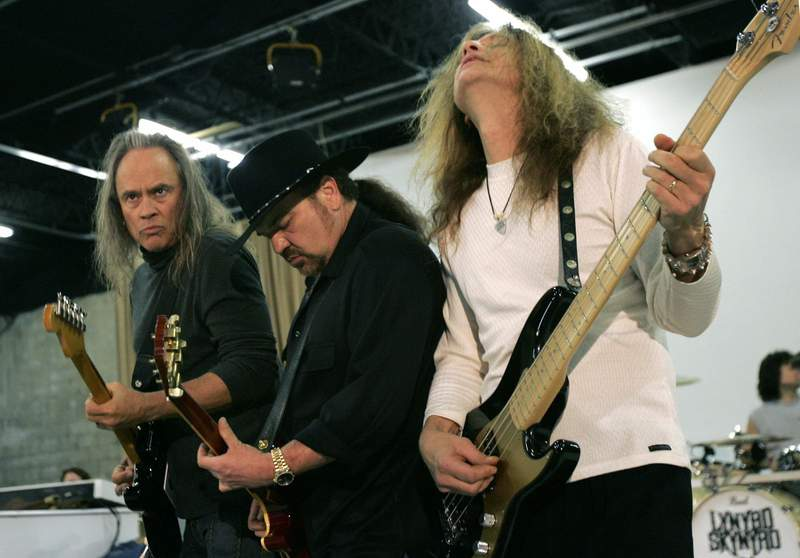 FILE - In this Friday, Feb. 4, 2005 file photo, Members of Lynyrd Skynyrd, from left, Rickey Medlocke, Gary Rossington and Ean Evans, practice at the Jacksonville Production Studio in Jacksonville, Fla. for their Saturday performance as part of the Super Bowl concert series. Lynyrd Skynyrd has pulled out of the Pro Football Hall of Fame concert after guitarist Rickey Medlocke tested positive for COVID-19, Saturday, Aug. 7, 2021. The band was set to co-headline the concert Monday night with Brad Paisley. According to a band statement, Medlockes positive test forced the groups withdrawal. (AP Photo/Ann Heisenfelt, File)