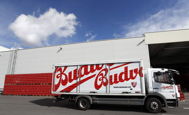 """FILE - In this file photo taken Monday, March 11, 2019, a truck drives past cases of beer at the Budejovicky Budvar brewery in Ceske Budejovice, Czech Republic. Budvar, the Czech brewer that has been in a long legal dispute with U.S. giant Anheuser-Busch over use of the """"Budweiser"""" brand, increased its net profit by almost 10% last year amid record output as the pandemic saw people drink less in bars and more at home. Budejovicky Budvar NP, a 125-year-old state-owned brewery, said Monday July 12, 2021, its net profit reached 305 million crowns ($14 million) in 2020. (AP Photo/Petr David Josek, FILE)"""