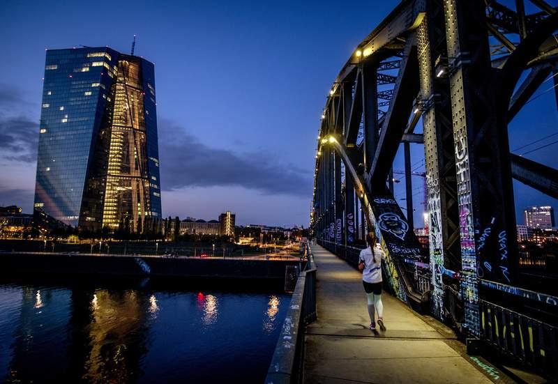 A woman walks over a bridge near the European Central Bank, left, in Frankfurt, Germany, Wednesday, Sept. 30, 2020. (AP Photo/Michael Probst)