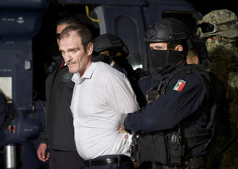 "FILE - In this June 15, 2016 file photo provided by the Mexican Attorney General's Office, Hector ""El Guero"" Palma, or Blondie, one of the founders of the Sinaloa Cartel, is escorted in handcuffs from a helicopter at a federal hangar in Mexico City, after serving almost a decade in a U.S. prison and transported to another maximum-security lockup to await trial for two murders. (Mexico's Attorney General's Office via AP, File)"