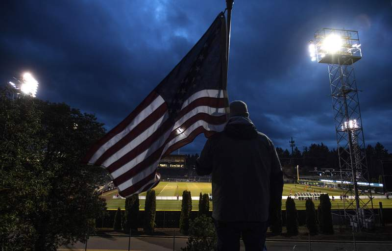 FILE - In this Wednesday, March 11, 2020 file photo, a man holds an U.S. flag as he watches the a United Soccer League match in Tacoma, Wash. In a matter of days, millions of Americans have seen their lives upended by measures to curb the spread of the new coronavirus in mid-March. (Joshua Bessex/The News Tribune via AP)