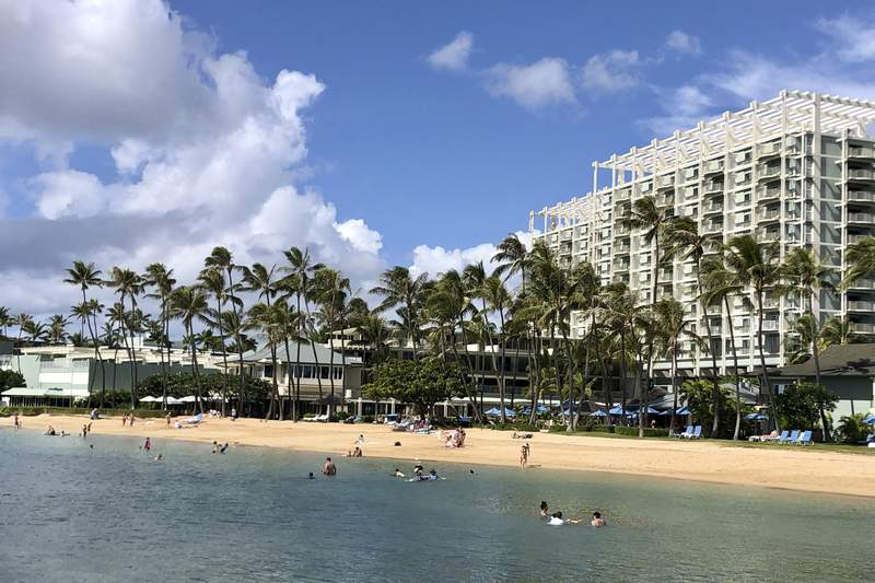 FILE - In this Sunday, Nov. 15, 2020, file photo, people are seen on the beach and in the water in front of the Kahala Hotel & Resort in Honolulu. The Honolulu Medical Examiner's office has identified the U.S. Navy sailor who shot and killed himself at the luxury resorts after a standoff with police. (AP Photo/Jennifer Sinco Kelleher,File)