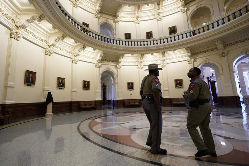 Texas Department of Safety officers stand watch over the Texas Capitol, Wednesday, Aug. 11, 2021, in Austin, Texas. Officers of the Texas House of Representatives delivered civil arrest warrants for more than 50 absent Democrats on Wednesday as frustrated Republicans ratcheted up efforts to end a standoff over a sweeping elections bill that stretched into its 31st day. (AP Photo/Eric Gay)