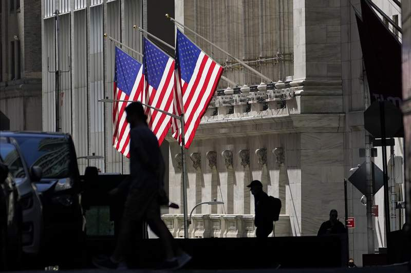 FILE - In this Oct. 14, 2020 file photo, pedestrians pass the New York Stock Exchange. After Donald Trump shocked markets by winning the presidency four years ago, investors quickly agreed on which stocks would benefit most from his election. But four years later, many of those stocks have since faded back, and stocks that were afterthoughts have become the market's leaders.   (AP Photo/Frank Franklin II)