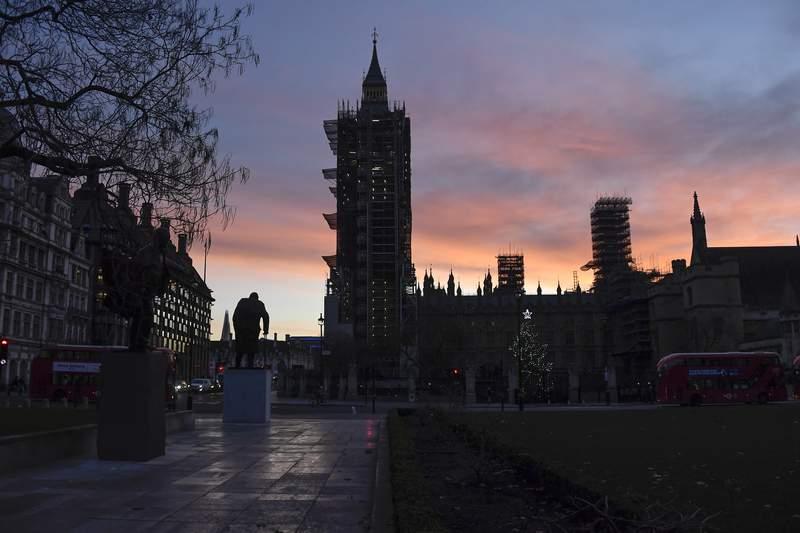 The sun rises over the Parliament Square, in London, Saturday, Dec. 5, 2020. (AP Photo/Alberto Pezzali)