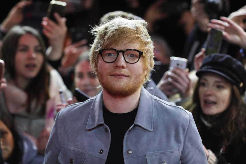FILE - In this Friday, Feb. 23, 2018 file photo, singer-songwriter Ed Sheeran arrives for the screening of the film 'Songwriter' during the 68th edition of the International Film Festival Berlin, Berlinale, in Berlin, Germany. Sheeran is the new shirt sponsor for third-division English soccer club Ipswich, it was announced Thursday, May 6, 2021. The Shape of You singer signed a one-year deal to sponsor the mens and womens shirts next season. The 30-year-old musician grew up in the area and is a longtime Ipswich fan.(AP Photo/Markus Schreiber, file)